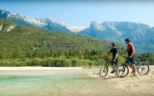Bike tour Soča Valley two bikers by Soča river