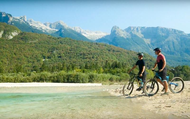 Kolesarja ob Soči in v ozadju Slovenske Alpe